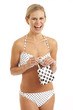 Young woman in white bikini with polka dots holding gift bag