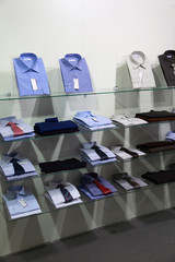 Fashionable shirts with ties lie on glass shelves in  shop