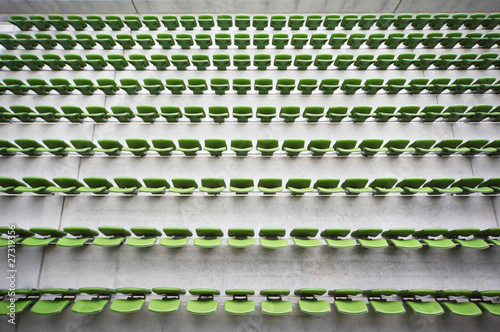 Rows of folded, green, plastic seats in empty stadium.