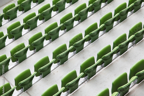 Many rows of green, plastic, folding seats in empty stadium.