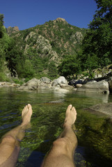 Man bating in a river in front of the mountains