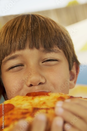 Boy Eating A Piece Of Pizza