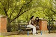 Two Young Women Sitting On Park Bench