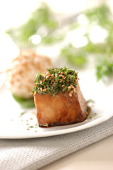 cube of caramelized grouper fish with soya and honey, topped with herbs and sesame seeds