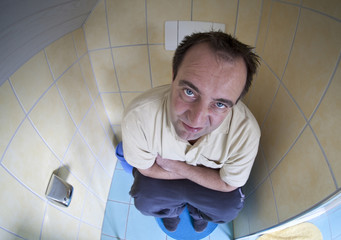after a sleepless night with diarrhea - man sitting on toilette