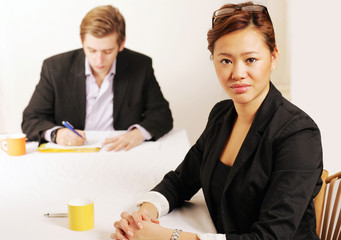 Serious businesswoman in meeting, colleague in background