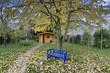 Garten im Herbst mit blauer Gartenbank und Gartengeräten
