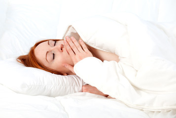 yawning young woman relaxing in white bedding