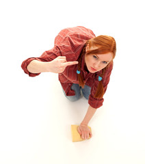 furious young woman washing floor by sponge