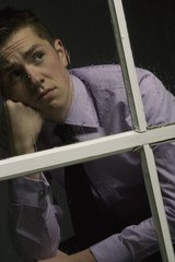 Unhappy Man Looking Out A Window