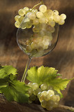 wine glass filled with bunch of white grapes