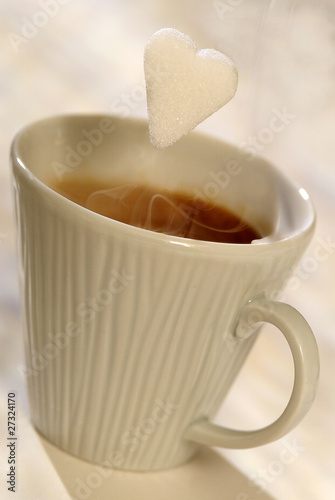 sugar lump falling into cup of coffee
