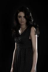 Portrait of a young seductive brunette over black