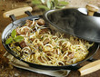 Beef with onions and chinese noodles cooked in a wok
