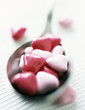 spoonfull of pink sweets in the shape of a heart