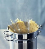 Cooking spaghettis in a cooking pot
