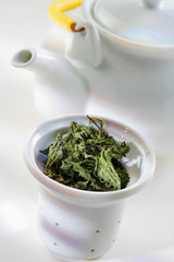 Loose tea in sieve and teapot