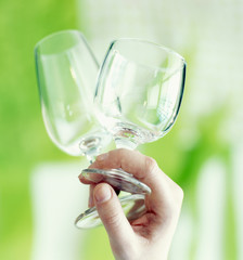 Two stemmed glasses in a hand