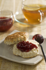 Scone with redcurrant jam and tea