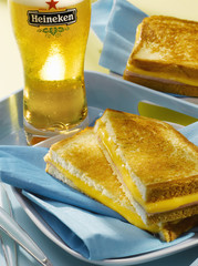 ham and cheddar toasted sandwich and glass of beer