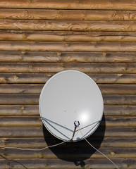 Спутниковая телевизионная антенна на стене.деревянного дома.