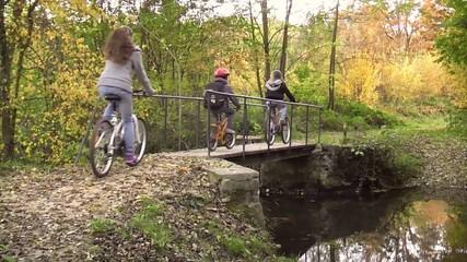 Trois enfants traversant un pont en vélo