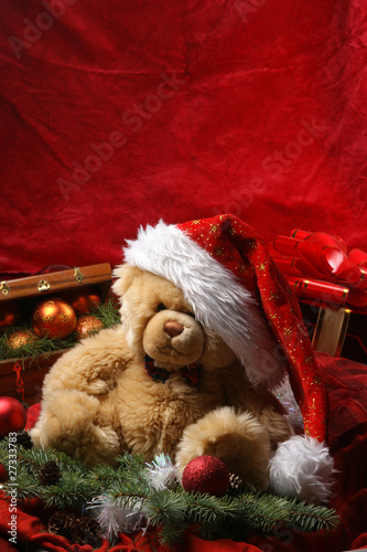 A cute teddy bear in a Christmas hat on a red silk background