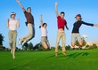 group of young people jumping outdoors grass