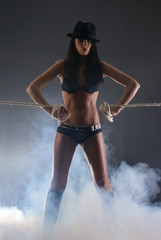 A young woman in dark erotic lingerie on a foggy background
