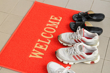 Pairs of Shoes  At The Doorstep With Welcome Mat