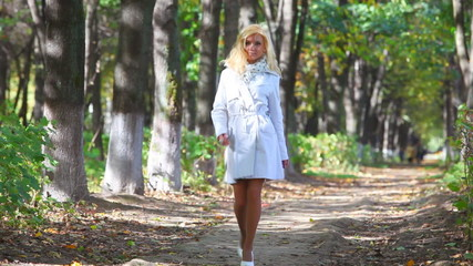 Young woman walking in park.