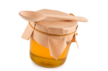 Honey in jar, wooden spoon, close up, isolated.