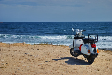 White motor scooter with sea in background