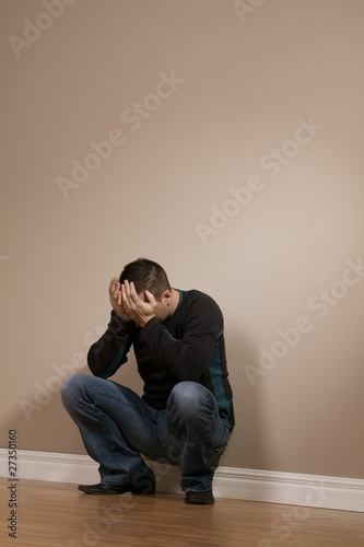 Man Crouching With Hands Over Face