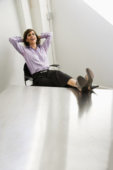 Female office worker relaxing, feet up on table