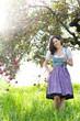 Frau mit Glas vor Apfelbaum