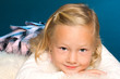 kleines blondes Mädchen liegt auf einem weissen Fell
