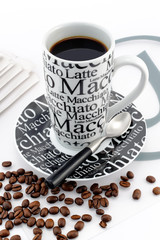 Stylish balck and white coffee mug with brown coffee beans