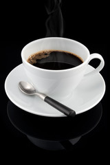 Cup of hot streaming coffee over black background
