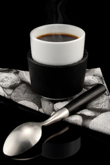 Hot streaming cup of expresso over black background