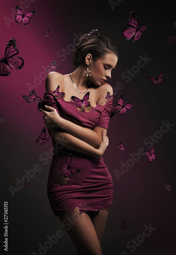 Conceptual image of young brunette beauty and violet butterflies