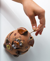a woman drops a coin into piggy bank