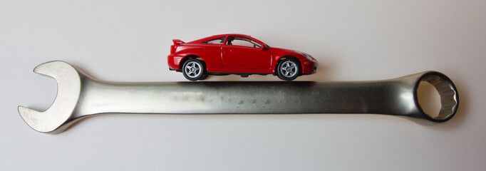 a small red car on a steel wrench