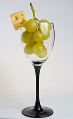 glass with white grapes and a cheese cube
