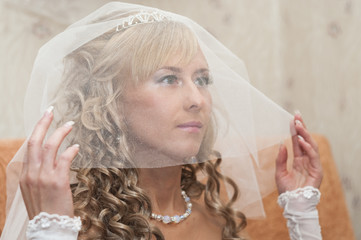 Portrait of young beautiful bride with blonde curly hair in veil