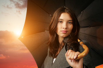 Female with black umbrella on beautiful sunset background