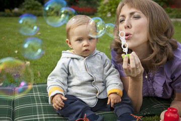 Mother and baby playing bubbles in the garden