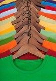 Many vibrant t-shirts on wooden hangers