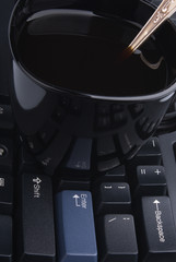 Cup of coffee on a computer keyboard, business still-life