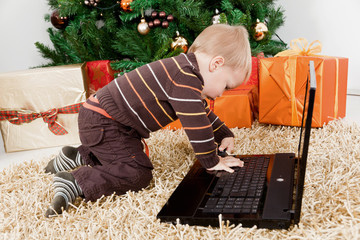 Baby boy playing with a laptop at christmas